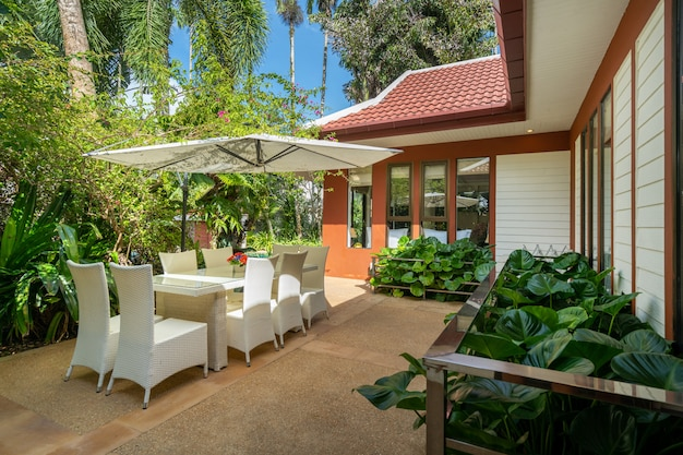 Das außendesign von haus, haus und villa verfügt über eine terrasse, einen tisch im freien, einen stuhl, einen sonnenschirm und einen garten