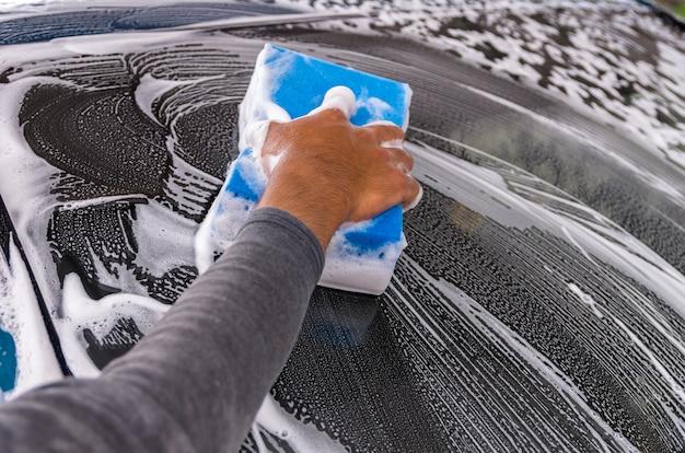 Das auto an der waschanlage säubern, autopflegekonzept, fokussieren an hand