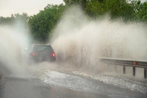 Das auto läuft bei starkem regen in eine große pfütze, wasser spritzt über das auto.