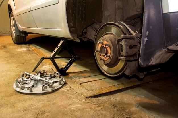 Das auto mit dem abgeschraubten wheell in der garage. reifenservice. reifenmontage.