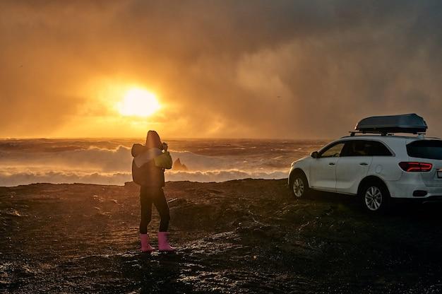 Das auto steht am meer. seestück, küste mit schwarzem vulkansand bei sonnenuntergang.