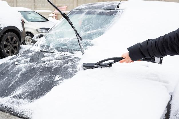 Das auto vom schnee reinigen