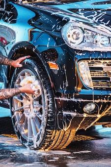 Das auto waschen. waschen eines schwarzen autos bei einer autowäsche. sauberes auto
