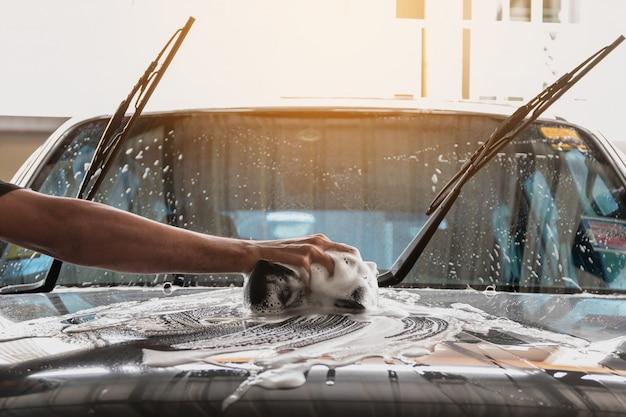 Das autowaschpersonal benutzt einen mit wasser und seife angefeuchteten schwamm, um das auto zu reinigen.