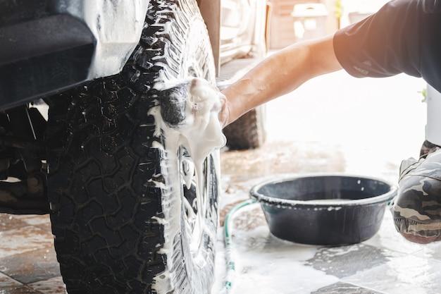 Das autowaschpersonal benutzt einen mit wasser und seife angefeuchteten schwamm, um die räder des autos zu reinigen.