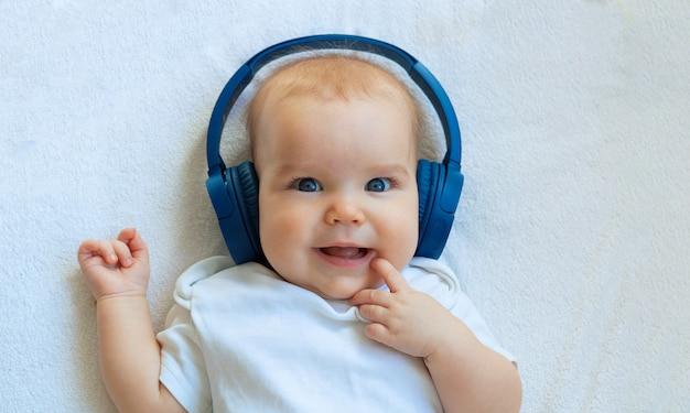 Das baby hört musik in drahtlosen blauen kopfhörern und lächelt