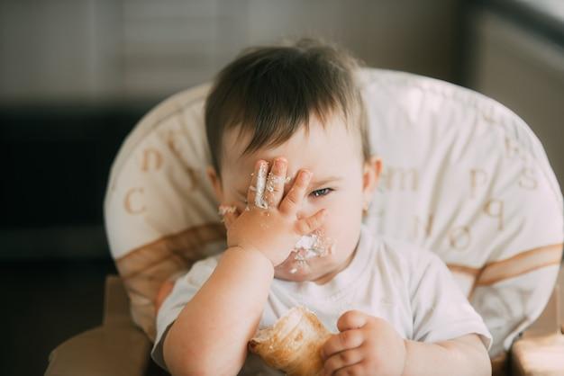 Das baby in der küche isst gierig leckere sahnekegel, die mit vanillecreme gefüllt sind. hände verschmieren das gesicht