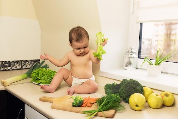 Das baby in der windel sitzt auf dem küchentisch. ein kind spielt und hat spaß mit frischem bio-gemüse und obst.