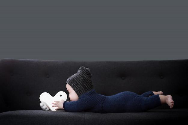 Das baby liegt auf dem schwarzen sofa und hält die puppe.