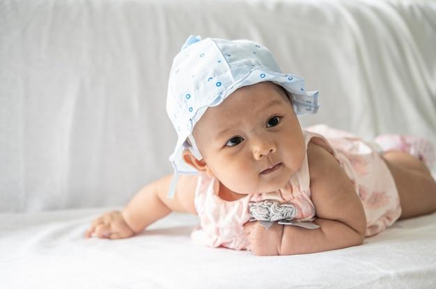 Das baby liegt mit dem gesicht nach unten auf dem bett.