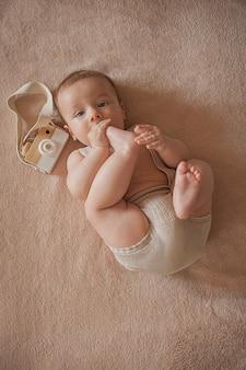 Das baby saugt zehen liegt auf einem beigen hintergrund