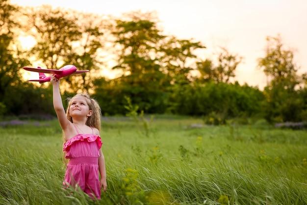 Das baby startet ein rosa flugzeug auf dem hintergrund des waldes und des hohen grases. spielen mit einem rosafarbenen flugzeug, das einen rosafarbenen anzug trägt