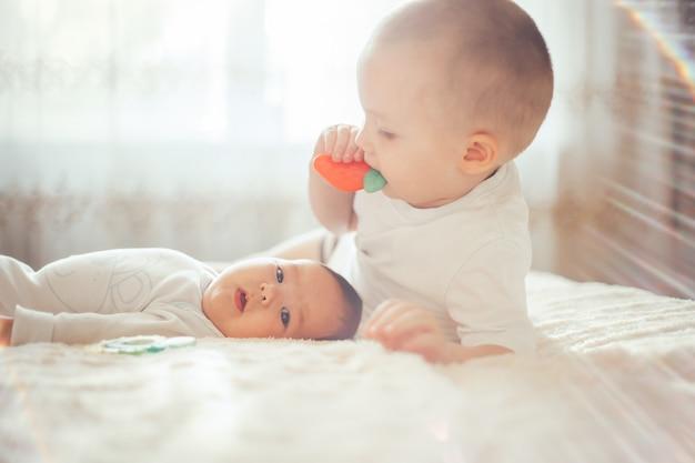 Das babykind, das auf bauch liegt, trug windel mit beißring