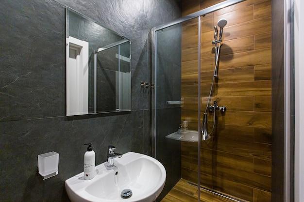 Das badezimmer ist mit einer dusche in dunklen farben ausgestattet und mit holz dekoriert
