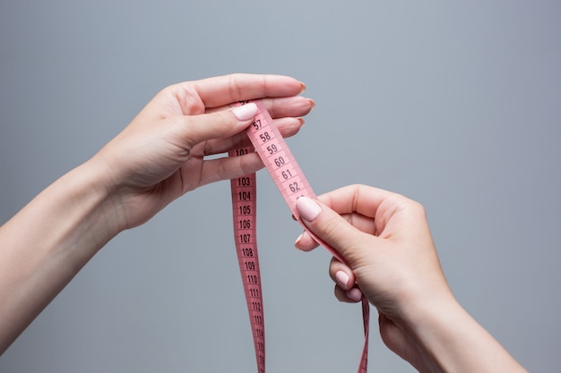 Das band in weiblichen händen auf grau. gewichtsverlust, diät und entgiftungskonzept