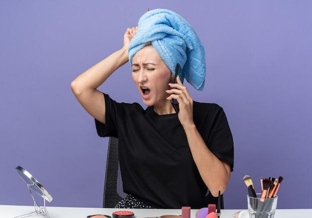 Das bedauerte junge schöne mädchen sitzt am tisch mit make-up-tools und wischt sich die haare im handtuch ab, spricht am telefon und legt die hand auf den kopf, isoliert auf blauem hintergrund