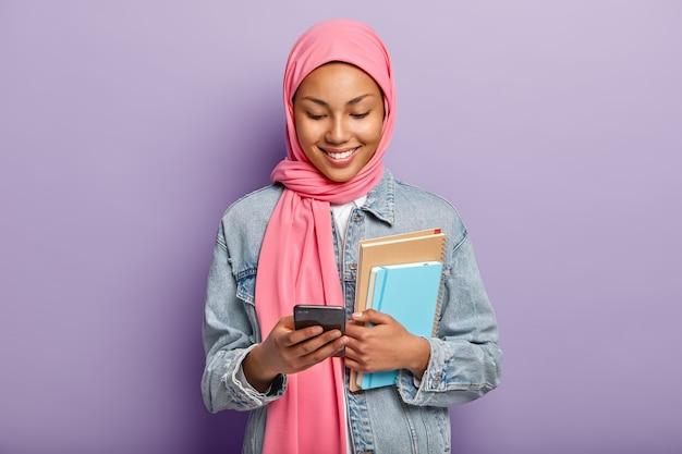 Das begeisterte muslimische schulmädchen sieht sich fotos in sozialen netzwerken an, hält moderne mobiltelefone und sieht sich lustige videoinhalte an