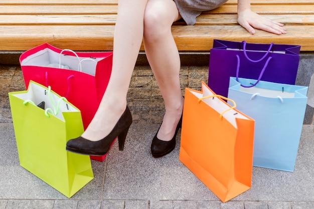 Das bein der frau mit bunten einkaufstaschen