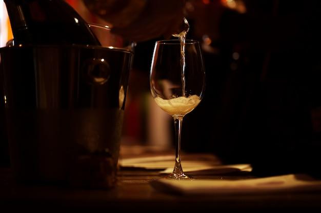 Das beleuchtete weinglas steht auf dem tisch und ein tropfen rosa champagner wird hineingegossen.