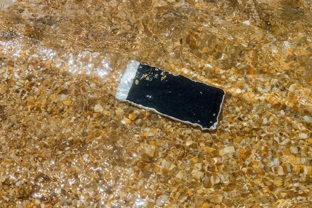 Das beschädigte smartphone ließ bei überschwemmung des ozeans nasses wasser fallen
