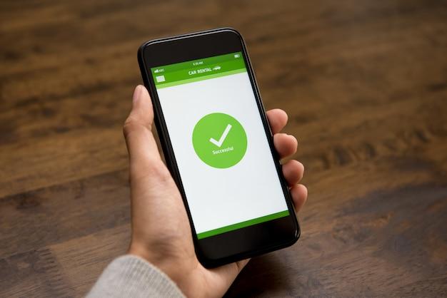 Das bestätigungszeichen für die erfolgreiche online-autovermietung wird auf dem bildschirm des smartphones angezeigt