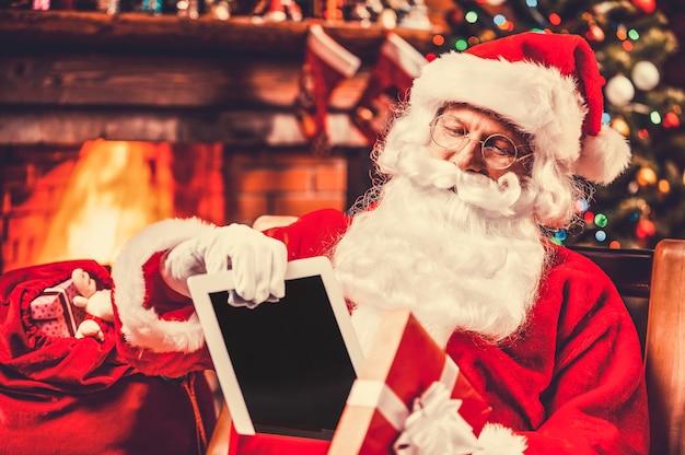Das beste geschenk! der fröhliche weihnachtsmann legt ein digitales tablet in die geschenkbox und lächelt, während er an seinem stuhl mit weihnachtsbaum im hintergrund sitzt