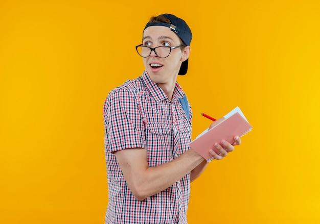 Das betrachten der seite beeindruckte den jungen studentenjungen, der brille und kappe trägt, die etwas auf notizbuch schreiben