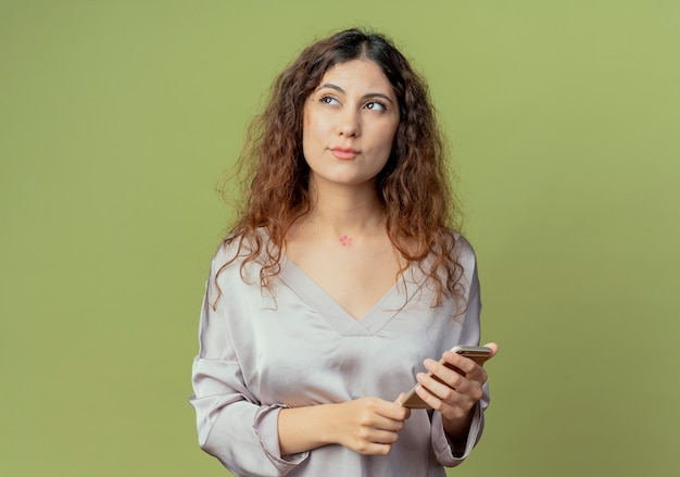 Das betrachten der seite beeindruckte junge hübsche weibliche büroangestellte, die telefon lokalisiert auf olivgrüner wand hält