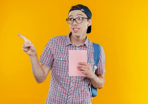 Das betrachten der seite erfreute jungen studentenjungen, der rucksack und brille und kappe hält, die notizbuch und punkte zur seite hält
