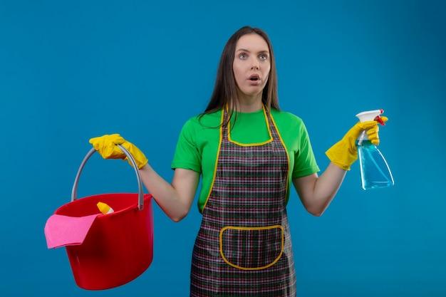 Das betrachten der seite überraschte das reinigen der jungen frau, die uniform in den handschuhen hält, die reinigungswerkzeuge und reinigungsspray auf isolierter blauer wand halten