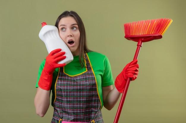 Das betrachten der seite überraschte das reinigen der jungen frau, die uniform in den roten handschuhen hält, die mopp halten, legte reinigungsmittel auf wange auf ihrer hand auf isolierter grüner wand