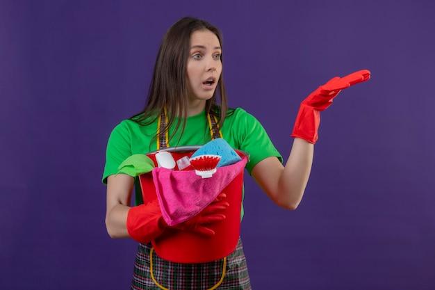 Das betrachten der seite überraschte das reinigen der jungen frau, die uniform in den roten handschuhen hält, die reinigungswerkzeuge halten, die hand auf isolierter lila wand heben