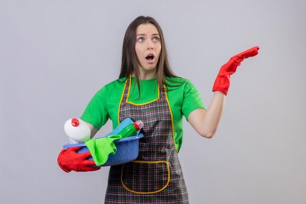 Das betrachten der seite überraschte das reinigen der jungen frau, die uniform in den roten handschuhen hält, die reinigungswerkzeuge halten, die hand auf isolierter weißer wand heben