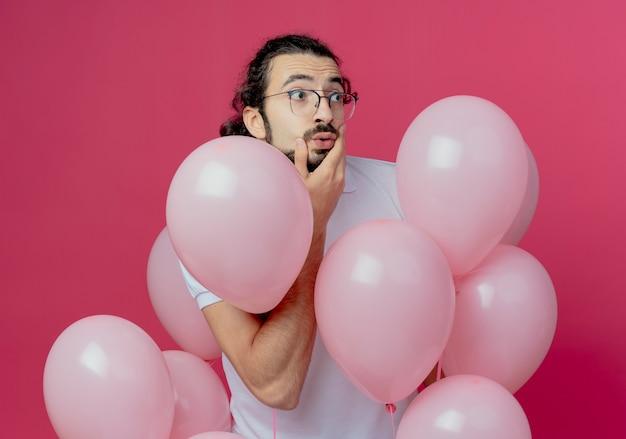 Das betrachten der seite überraschte gutaussehenden mann, der eine brille trägt, die unter luftballons steht und hand auf wange lokalisiert auf rosa hintergrund setzt