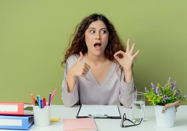 Das betrachten der seite überraschte junge hübsche weibliche büroangestellte, die am schreibtisch mit bürowerkzeugen sitzt, die okey geste und ihren daumen oben lokalisiert auf olivgrünem hintergrund zeigen