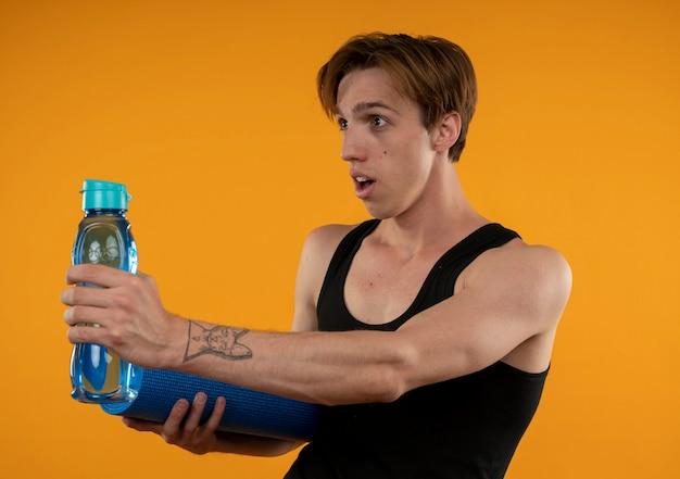 Das betrachten der seite überraschte jungen sportlichen kerl, der yogamatte mit wasserflasche an der seite lokalisiert auf orange wand heraushält