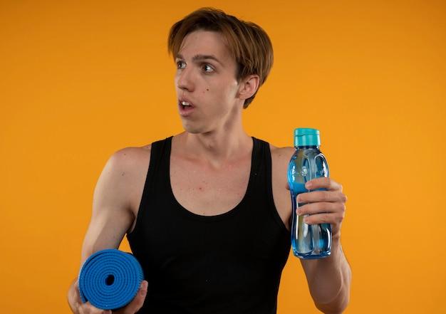 Das betrachten der seite überraschte jungen sportlichen kerl, der yogamatte mit wasserflasche lokalisiert auf orange wand hält