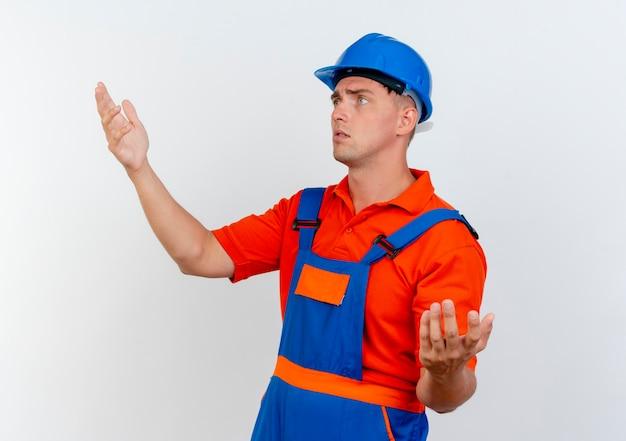 Das betrachten der seite verwirrte jungen männlichen baumeister, der uniform und schutzhelm trägt, der vorgibt, etwas zu halten