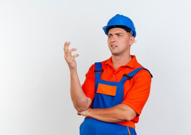 Das betrachten der seite verwirrte jungen männlichen baumeister, der uniform und sicherheitshelm trägt, die hand heben