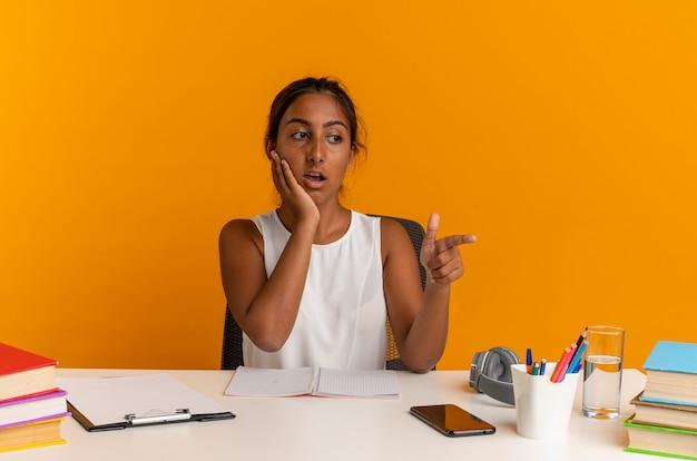 Das betrachten der seite verwirrte junges schulmädchen, das am schreibtisch mit den schulwerkzeugpunkten an der seite sitzt und hand auf wange legt