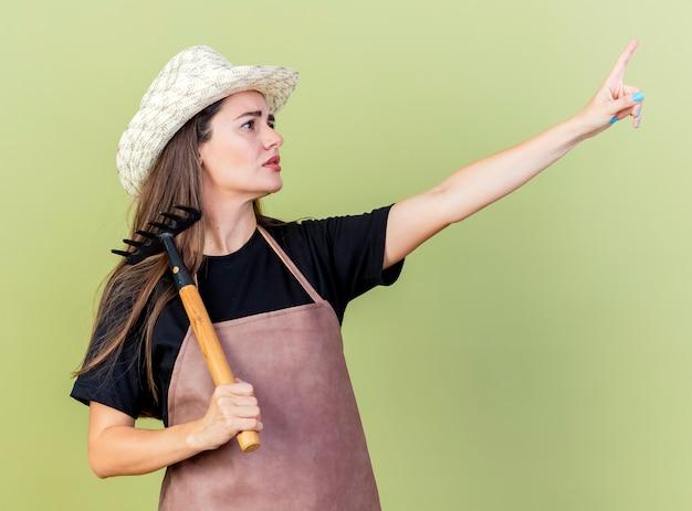 Das betrachten der seite verwirrte schönes gärtnermädchen in der uniform, die gartenhut trägt, der rechen auf schulter und punkte auf seite lokalisiert auf olivgrünem hintergrund setzt