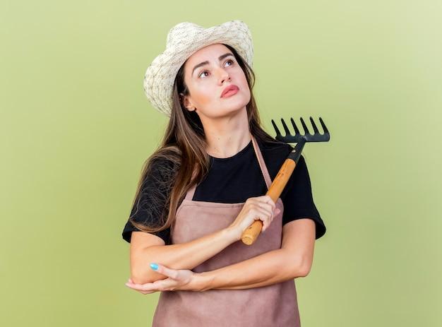 Das betrachten des erfreuten schönen gärtnermädchens in der uniform, die gartenhut hält, hält rechen lokalisiert auf olivgrünem hintergrund