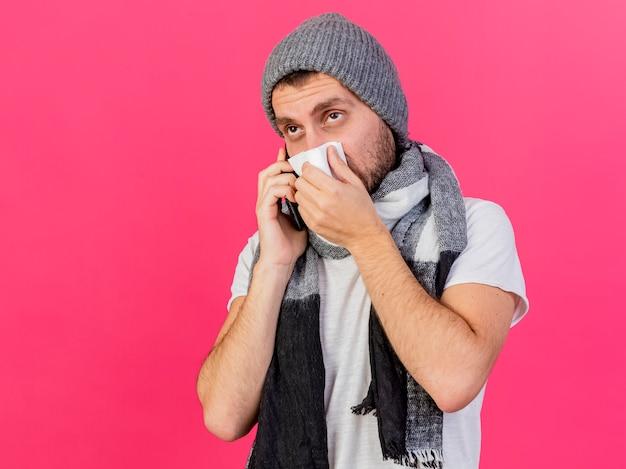 Das betrachten des jungen kranken mannes der seite, der wintermütze mit schal trägt, spricht am telefon und wischt nase mit serviette ab, die auf rosa hintergrund mit kopienraum isoliert wird