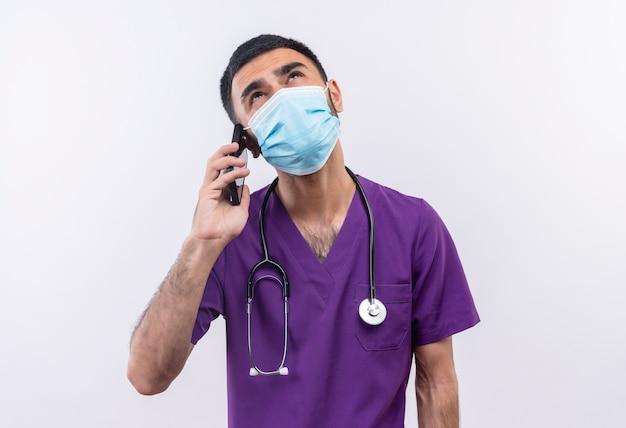 Das betrachten des jungen männlichen arztes, der lila chirurgenkleidung und medizinische stethoskopmaske trägt, spricht am telefon auf lokalisiertem weißem hintergrund