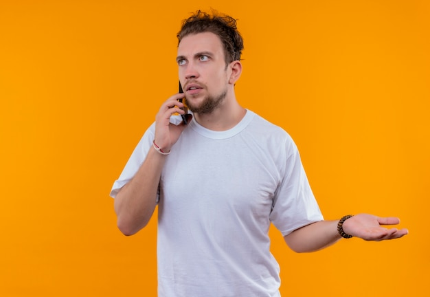 Das betrachten des jungen mannes der seite, der weißes t-shirt trägt, spricht am telefon, das hand auf seite auf lokalisiertem orange hintergrund hält