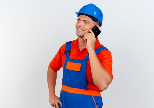 Das betrachten des lächelnden jungen männlichen baumeisters der seite, der uniform und schutzhelm trägt, spricht am telefon und legt hand auf hüfte