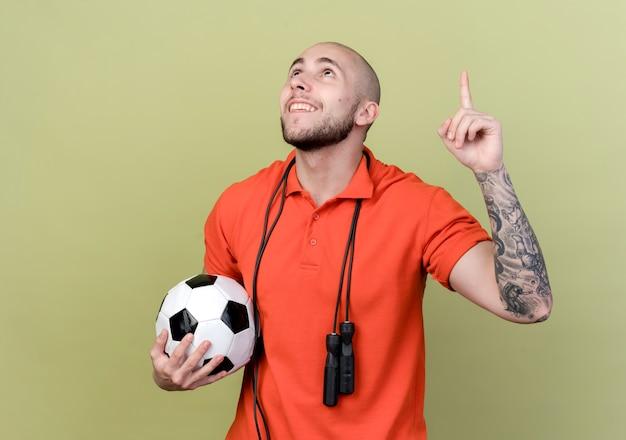 Das betrachten des lächelnden jungen sportlichen mannes zeigt auf das halten des balls mit dem springseil auf der schulter lokalisiert auf olivgrünem hintergrund