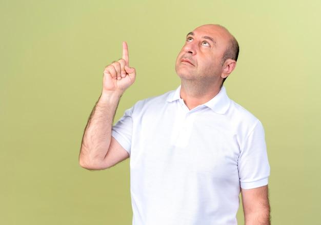 Das betrachten des reifen mannes zeigt oben auf der olivgrünen wand