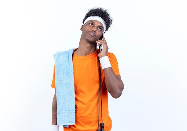 Das betrachten des traurigen jungen afroamerikanischen sportlichen mannes der seite, der stirnband und armband trägt, spricht am telefon mit handtuch und springseil auf schulter lokalisiert auf weißem hintergrund