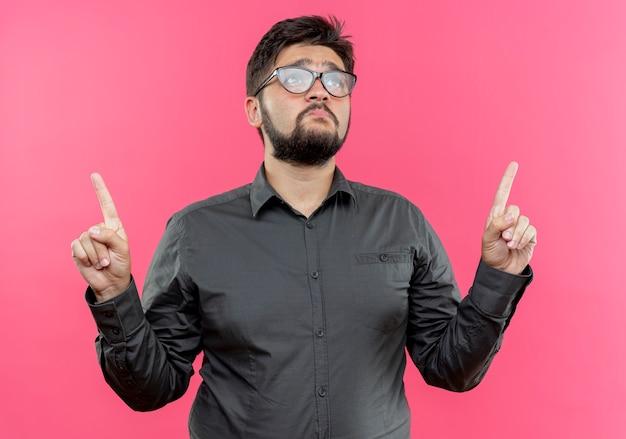 Das betrachten des traurigen jungen geschäftsmanns, der brillen trägt, zeigt oben auf rosa wand mit kopienraum